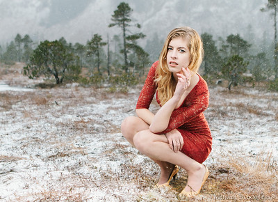 Young woman in red dress crouching on snow-covered ground in the winter