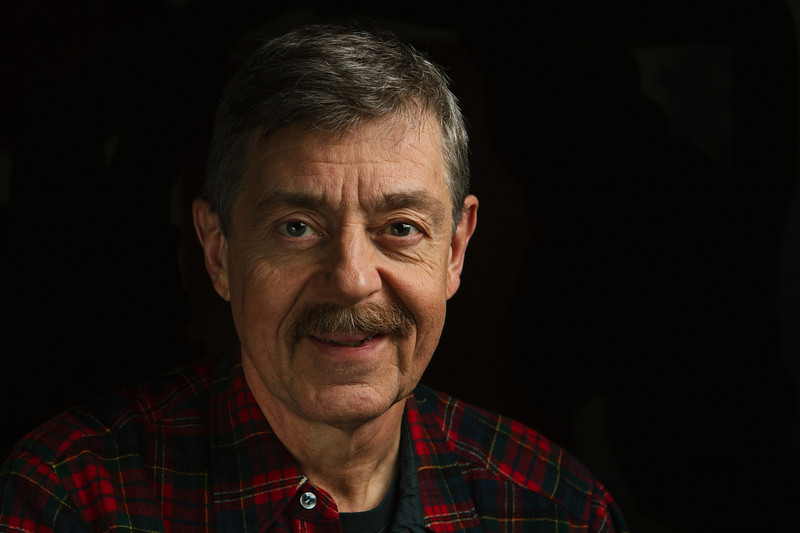 Portrait of an older man in plaid button-up shirt isolated on a black background