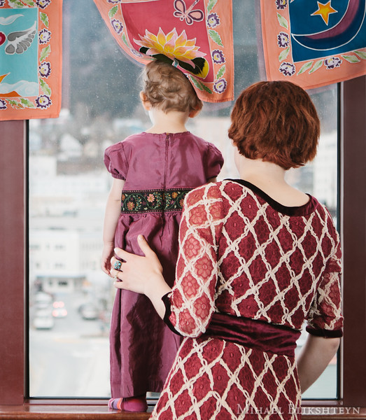 Young mother with her little daughter looking out the window
