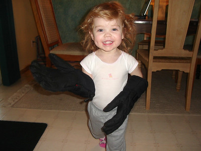 Wearing daddy's gloves.