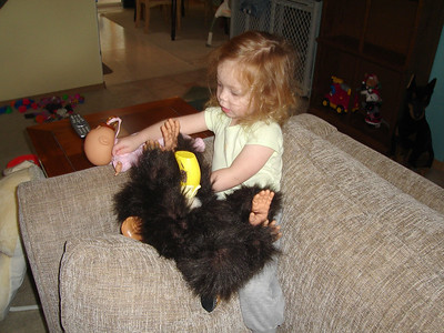 Feeding her monkey a bottle.