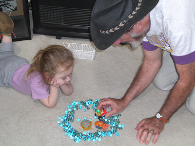 Kimber and Papa Ben playing with trucks and marbles.