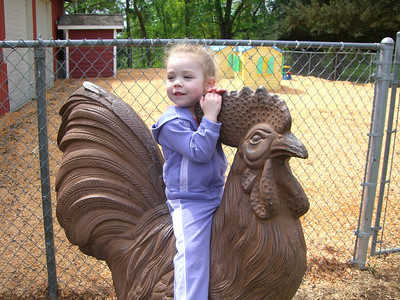 Riding the rooster outside the petting zoo at Jennings Park.