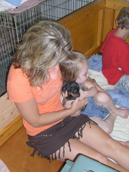 Kim holding Kimber and a puppy.