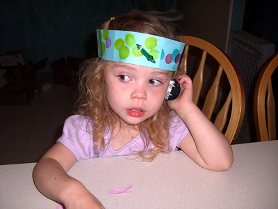 Talking on the phone with Grandmama Carol. Also wearing her crown that she made in daycare that day.