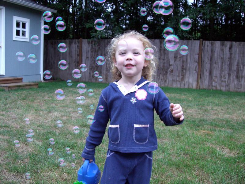 Running through bubbles in the backyard.