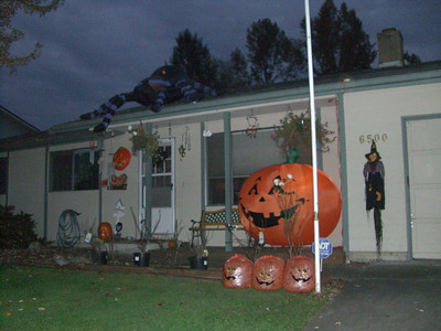 A house with a huge pumpkin and a bunch of other decorations.