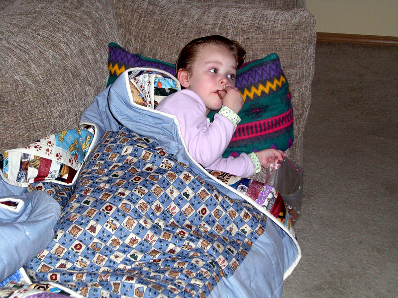 Lying on the couch with her new blanket made by Grandmama Carol.