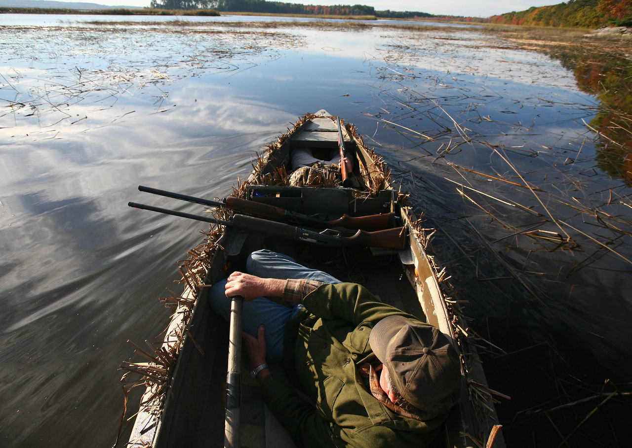 Two loaded shotguns at the ready, Al Hall silently skulls his gunning float through the waters of Merrymeeting Bay.