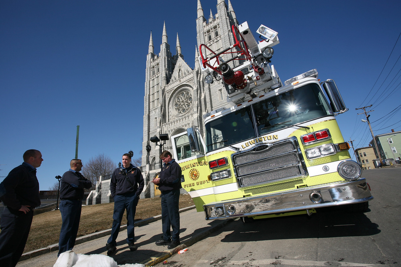 (Photo: Lincoln Benedict) Lewiston Fire Fighters wait outside the funeral of former Lewiston Police Chief Roland Dumais at the Basilica of Saints Peter and Paul on Saturday. They were to lead the funeral procession with the week old Pierce ladder truck.