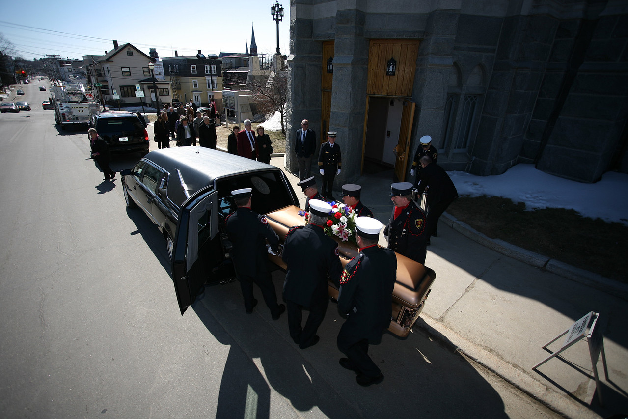 (photo: Lincoln Benedict)Former Lewiston Police Chief Roland Dumais' casket is placed inside a hearse outside the Basilica of Saints Peter and Paul after the funeral service.