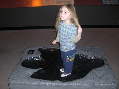 Standing in a dinosaur foot print at the Pacific Science Center.