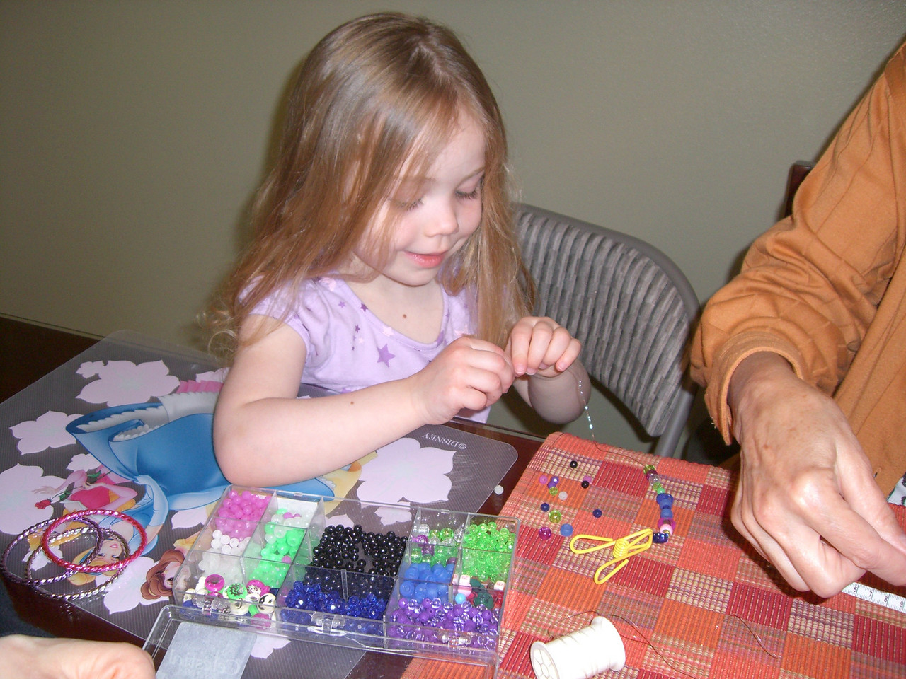 Making beaded necklaces and bracelets.