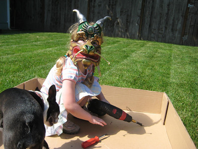 Drilling holes into a cardboard box...while wearing the dragon mask we bought her at Cirque du Soleil.  Interesting combination.