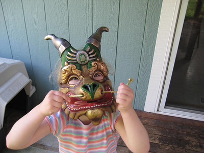Wearing the dragon mask we bought her at Cirque du Soleil.