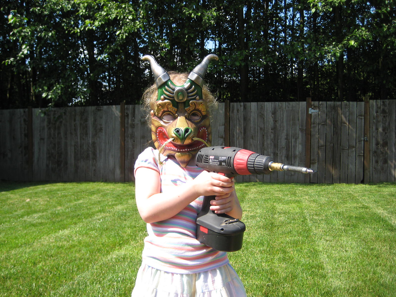 Wearing the dragon mask we bought her at Cirque du Soleil...while holding my drill. :)