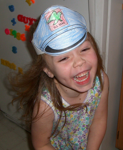 Giggling up a storm while posing for a picture with her 'mail carrier' hat made in daycare.