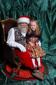 """She warmed up to Santa a lot faster this year then previously, but she refused to smile so I was standing behind the photographer saying """"I'm going to come sit on Santa's lap with you."""""""