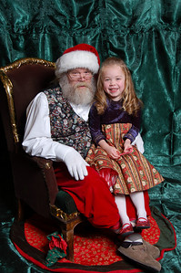 At this point I was standing behind the photographer waving my arms and being silly to get Kimber to crack one of her big smiles.  It worked, but then Santa wasn't smiling.  Oh well.