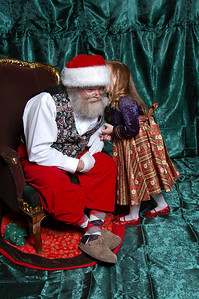 Whispering what she wants for Christmas in Santa's ear.  She didn't warm right up to him so this was the first step.
