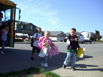 9.10.2009 - First day of kindergarten. Getting off the bus in the afternoon (that's Orlando, our neighbor, to her left).
