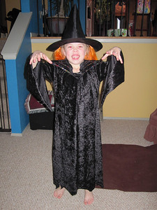 A scary little Kimber trying on her new witch costume, made by Grandmama Carol.