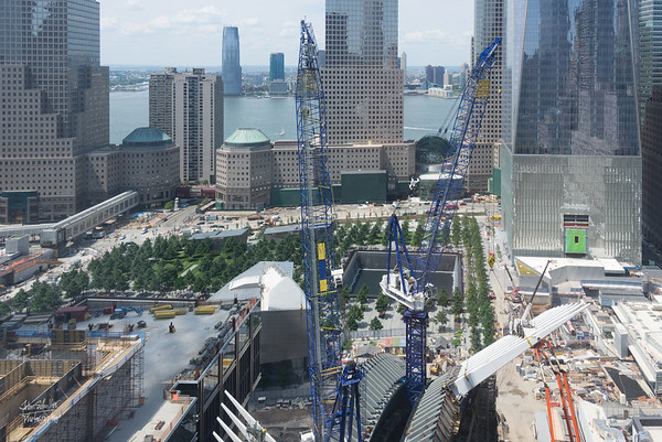 A view of the memorial site of the World Trade Centers, from the 31st floor of the Hilton Millineum.  Ther bottom of One WTC is the building on the right, with the green canopy in the front.  The skeleton of the new transportation center is rising in the front of the pciture.