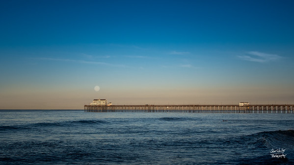 The Oceanside Dock reaches out to catch the Supermoon as it gently sets into the Pacific Ocean in the early morning.  Shot at Oceanside CA on February 1, 2018 © John Schiller Photography