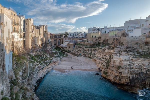 View of the wonderful small public beach of Lama Monachile, nestled between two high rocky walls, is also called Cala Porto..  Ponti di Polignano in the background