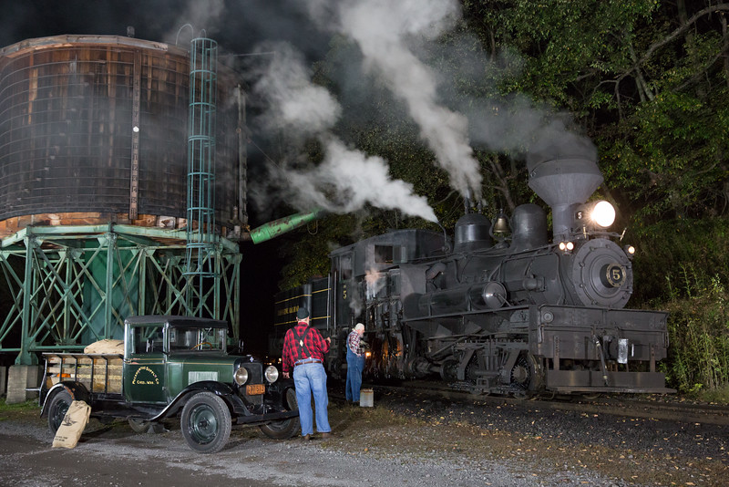 Matt Wilson motions towards T.C. as he oils Shay no. 5 during a night photo session.