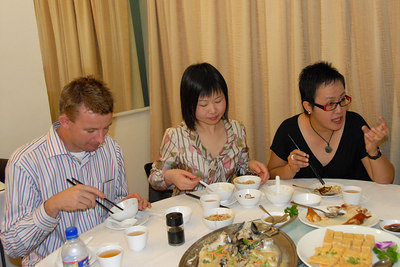 Patricia stressing a point over lunch while Jian and Danny dig into the food