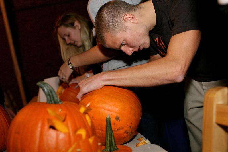 Mike Lutz '09 carves a pumpkin during the annual Pumpkin Bash philanthropy. <br /> <br /> Photo by Alex Turco