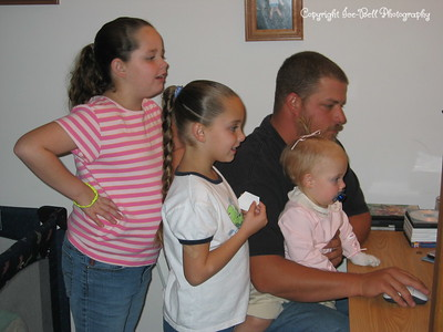 10/29/2005  From left to right.  Ashlynn, Baylee, Doug, and Hanna.  The three girls are my great Neices.  They are all watching something on the new computer I had just brought them.