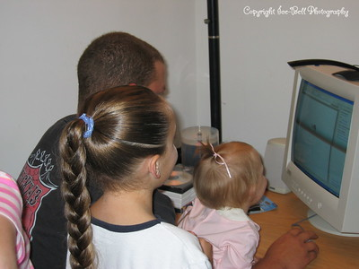 10/29/2005  Baylee Doug and Hanna watching the help character on the new PC.  They where entertaining Hanna with it.