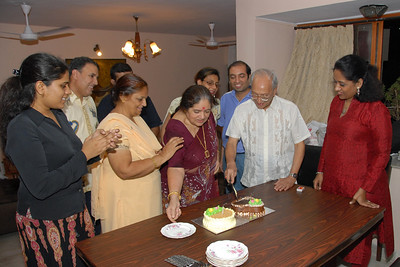 Papa cutting the cake while Amma helps out with the plates.