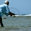 A Fishing guide in Honduras bends low to reduce his profile in order to try and avoid being seen by the bonefish that his has just cast to. He is fly-fishing for bonefish on the flats where stealth and precision of casting is important. His clothes mainly blue allow him to blend in quite well with the sky behind him.  His left hand is poised onthe line in preparation for a strike as there are bonefish approaching his fly. this is a crucial moment for fishermen