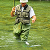 a fly-fisherman brings in a rainbow trout which he has just hooked on a dry fly