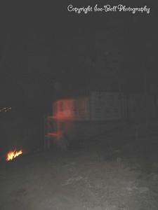 05/29/03  Other side view of the house at night.  You can see the fire that was set to burn away brush that evening.