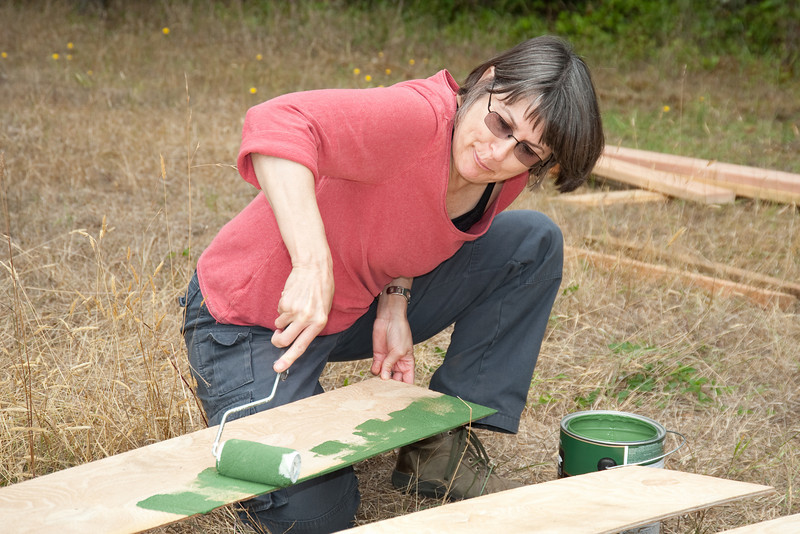 Jo Ann paints the exterior plywood that will form the yurt's drip ring.