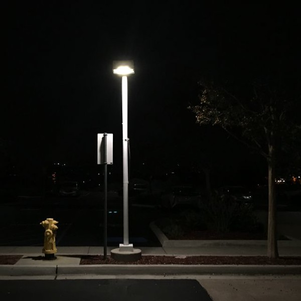 Photo of a streetlamp, a fire hydrant, and a tree, at night