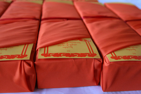 Traditional unbound books that are wrapped in red cloth with table of content slip showing.