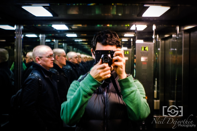 In an office lift with the Svein Army<br /> <br /> The start of the Fuji X-Pro1 Diaries.<br /> <br /> My girlfriend surprised me by buying me the Fuji X-Pro1 as a present for my 30th birthday (lucky me) and Svein in the background there also bought me a Fuji M Mount adapter so that I could attach my Leica lens to the system.<br /> <br /> What makes this photo, one of the very first I took, so unique, is the reflections of Svein in the background. Each one almost looks like a different person with a different pose.<br /> <br /> <br /> Fuji X-Pro1 + Leica Summarit 35mm 2.5