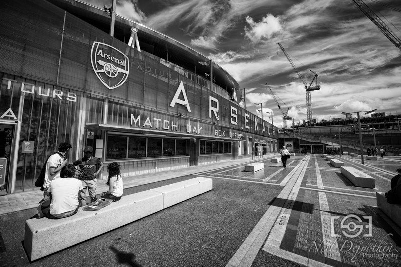 The Emirates Stadium, home of Arsenal Football Club.<br /> <br /> There's renovation work going on just by the stadium, where there building some new houses or something like that. I thought it would make a nice backdrop especially with such vibrant clouds filling the sky.<br /> <br /> I noticed the lines on the floor and decided to use that as a means to draw you into the background and give a sense of scale and drama.<br /> <br /> Nikon D800 + 14-24mm 2.8