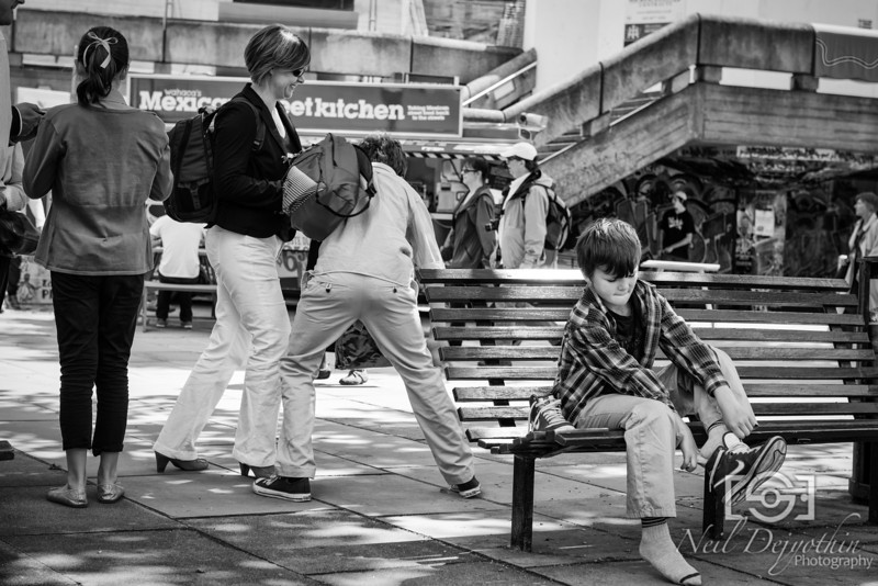 "Putting on your shoes<br /> <br /> The cool thing about the South Bank is there is just so much going on. There's lots of entertainers and acts that can be fun, but the normal civilians around there are just as interesting.<br /> <br /> Here, I sat opposite a couple of benches. Perfect for looking inwards rather than outwards onto the river. You can go relatively unnoticed and get nice angles.<br /> <br /> The boy putting on the shoes is connected to the people behind him, who are his family. The family were being playful behind, which went completely unnoticed to the boy who was putting on his shoes and that's what made the shot for me. By the time he turned around he never knew that playful moment existed, as they'd returned to a more normal mode of ""ready to go"" by the time he'd put his other shoe on.<br /> <br /> Nikon D800 + 24-70mm 2.8"