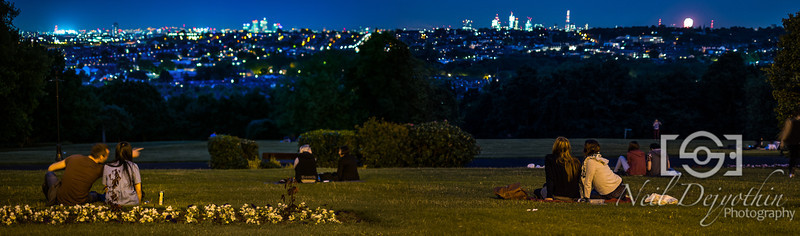 The London cityscape from Alexandra Palace.<br /> <br /> I placed my camera on a bit to keep it steady and took some long exposures to capture the beautiful blue night sky and all the lights from the buildings.<br /> <br /> Often times in situations like these, you see couples or friends talking about places or experiences in the capital.<br /> <br /> This was no different. The guy on the left was with his girlfriend, and the added movement and motion to the scene through him pointing something out to her helped add that story I was looking for.<br /> <br /> Fuji X-Pro1 + Fujinon 35mm 1.4
