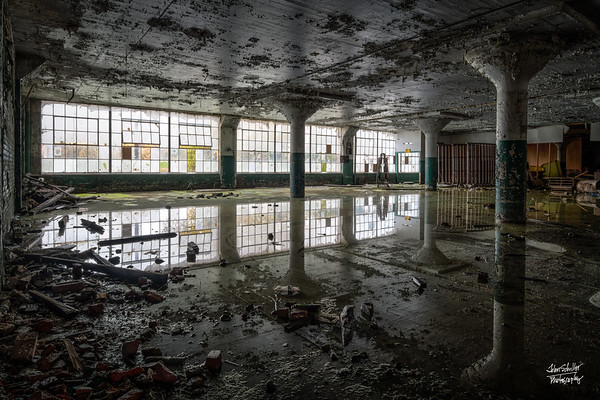 Don't be fooled.  This is not a two-story room!  Water covering much of the floor perfectly reflects the windows and pillars, enlarging the room before your eyes.     © John Schiller Photography