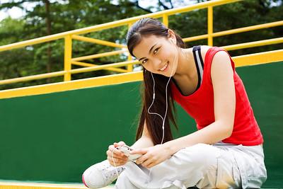 smiling girl listening music through here headphones