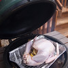 The setup: Large Big Green Egg loaded with lump charcoal and apple wood chips, topped with the ceramic plate setter, tin foil drip pan, grate, and the TURKEY.