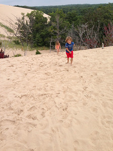 Ada and Dylan running up the hill of the dune.