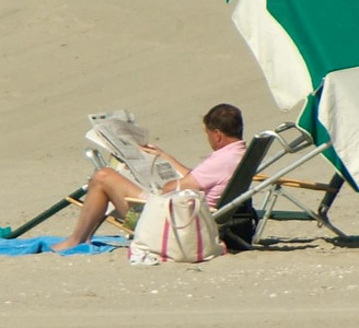 Ah yes the wonders of technology and a 300mm zoom lens with image stabilization!  what's he reading???